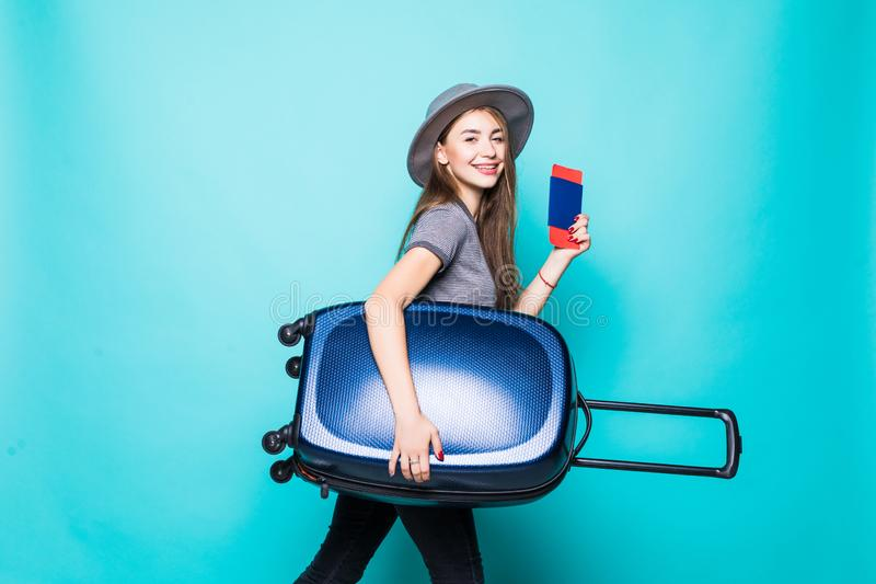 Travel and Lifestyle: Portrait of young woman holding passport with flying tickets standing with a suitcase over blue background. Portrait of young woman holding stock photos