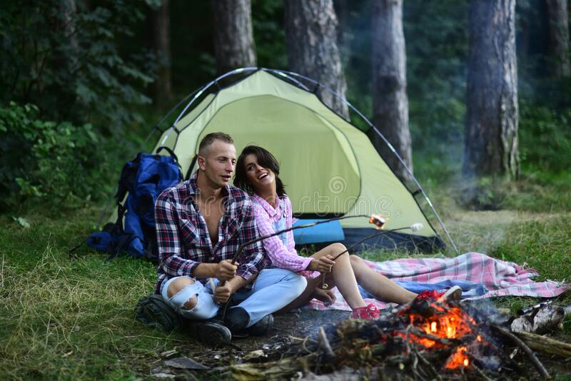 Travel, love and living in nature concept. Sensual young couple in love roasting sweet marshmallow in fire and have fun royalty free stock image