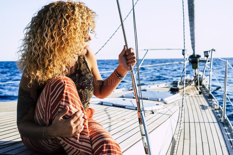 Travel and luxury lifestyle concept wtith beautiful blonde curly attractive woman sitting on the dock of a sail boat - people royalty free stock photo