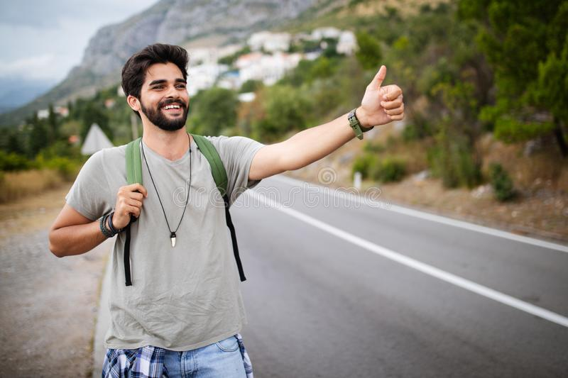 Travel man backpacking hitchhiking on road trip hitching a ride from car stock photos