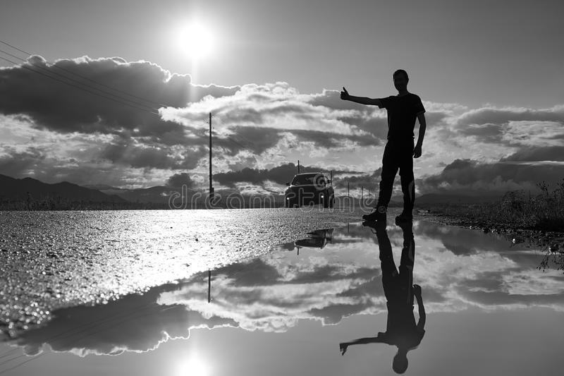 Travel man hitchhiking. Reflection in a puddle. Silhouette of man with a raised hand thumb up.  stock images