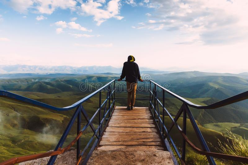 Travel man tourist alone on the edge viewing platform or observation point made from metal over amazing epic valley mountains royalty free stock image