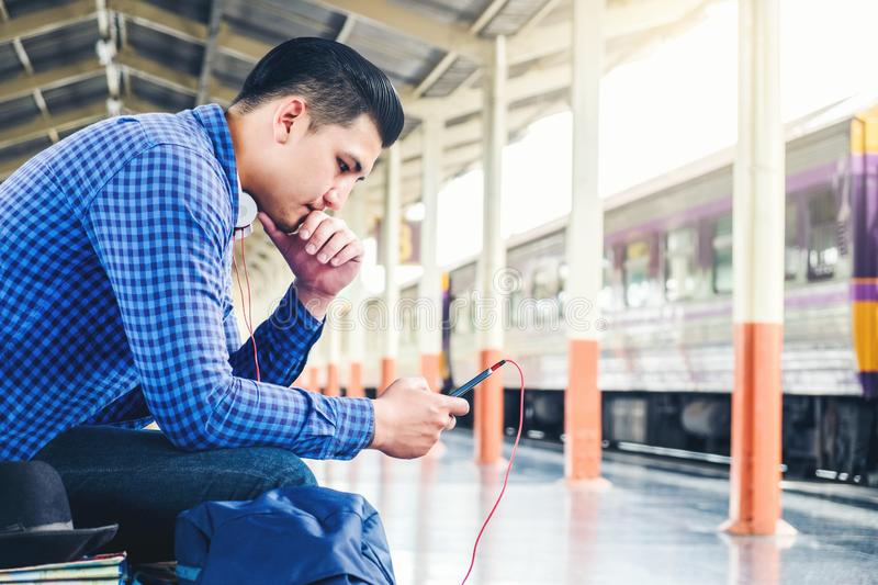 Travel man using mobile listening music phone and at train station stock image