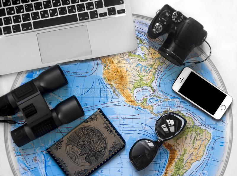 Travel map laptop computer keyboard personalized Russian glasses passport photo camera binoculars flat lay phone mobile royalty free stock photo