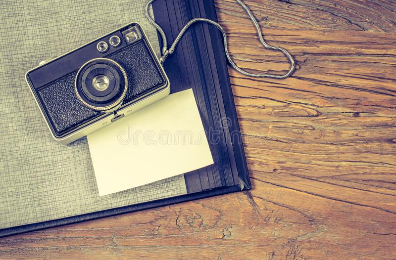 Travel memories concept: Flat lay of old camera and photo album with white blank paper for message. stock images