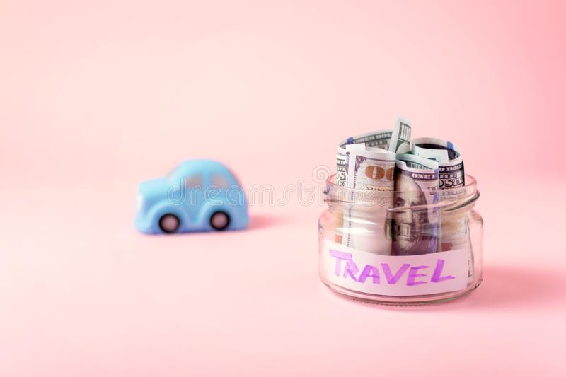 Travel money savings concept. Blue toy car and save money glass jar with dollars banknotes on pink background. Budget, coins, cash, destination, discover royalty free stock image