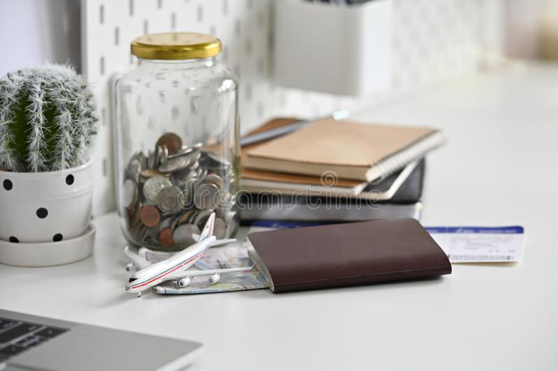 Travel money savings in a glass jar with passport, ticket and map on office desk.  royalty free stock photography