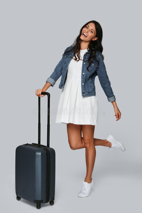 Travel mood. Full length of beautiful young woman smiling and looking at camera while standing against grey background stock photos