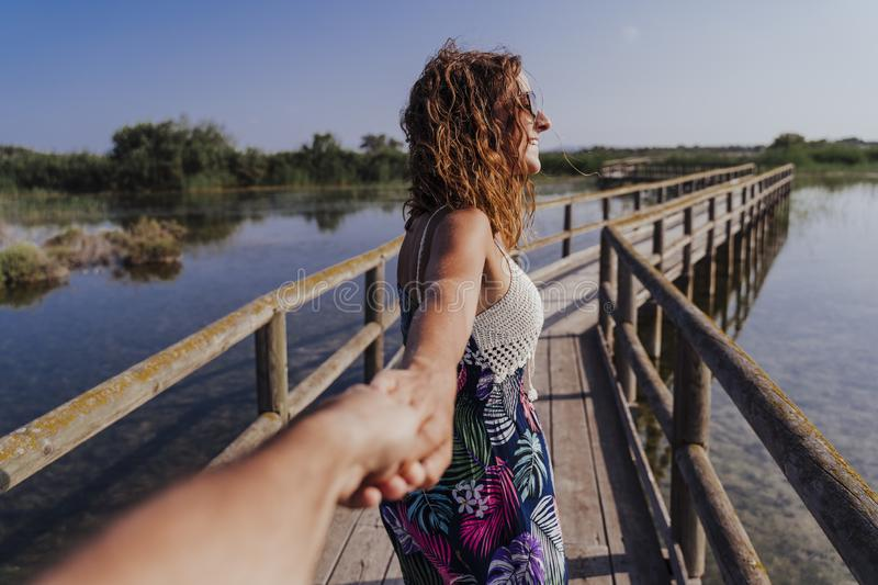 Travel nature follow me woman in a natural park holding hand of boyfriend following leading girlfriend walking. Tourism, love and royalty free stock photo