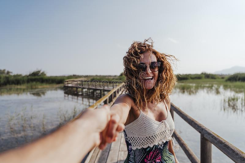 Travel nature follow me woman in a natural park holding hand of boyfriend following leading girlfriend walking. Tourism, love and stock photography