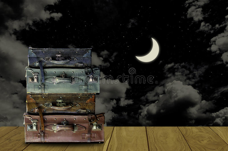 Travel at night concept, Vintage travel bag with moon in night. Sky background royalty free stock image