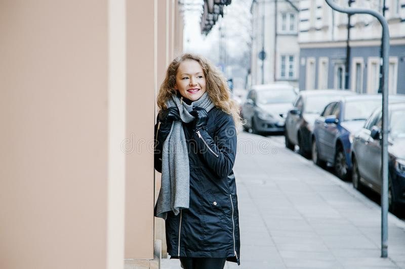 Travel the old city. A young woman travels. Market Square in Warsaw. Curly girl walks through the streets of the city. Poland royalty free stock images