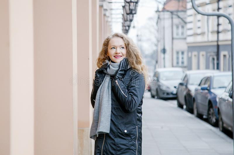 Travel the old city. A young woman travels. Market Square in Warsaw. Curly girl walks through the streets of the city. Poland royalty free stock photography