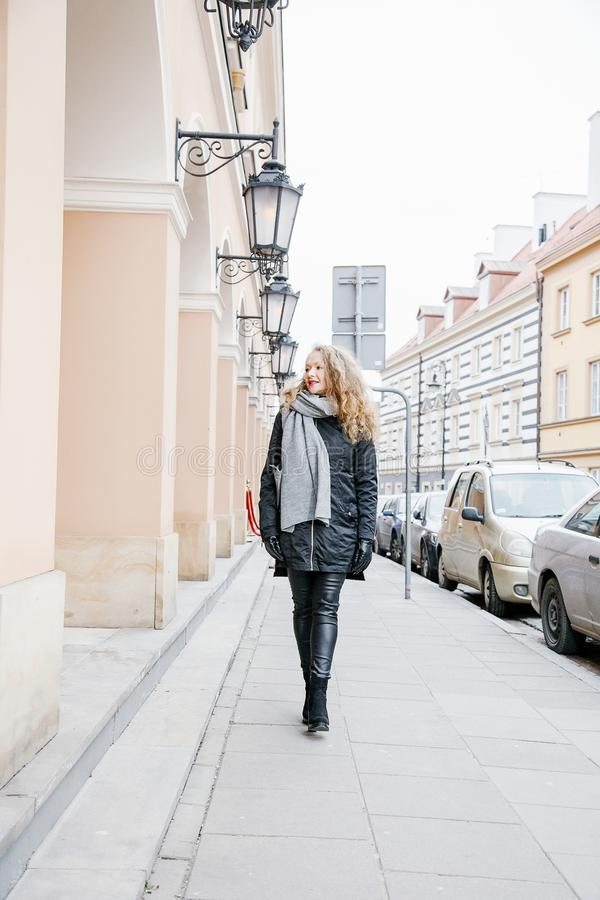 Travel the old city. A young woman travels. Market Square in Warsaw. Curly girl walks through the streets of the city. Poland stock photo