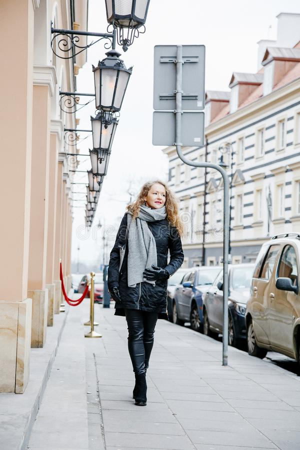 Travel the old city. A young woman travels. Market Square in Warsaw. Curly girl walks through the streets of the city. Poland royalty free stock photo