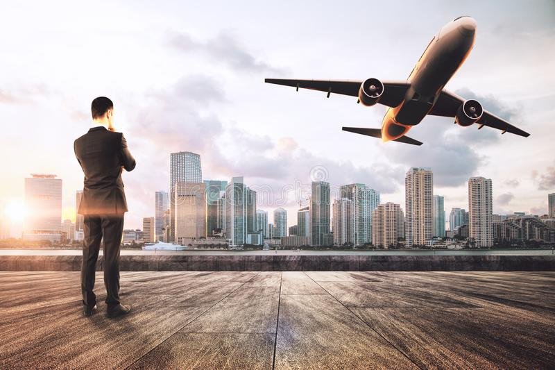 Travel and passenger concept. Young businessman on rooftop looking at flying airplane on sky and city background. Travel and passenger concept stock image