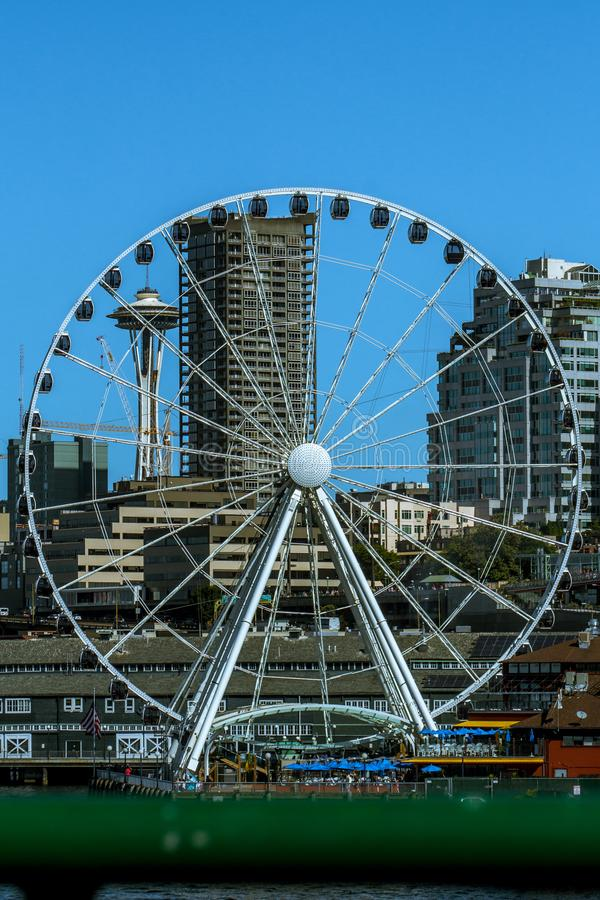 Seattle Great Wheel in front of the Space Needle with a blue sky as the background. Travel photo of the Great Wheel in Seattle that frames the Space Needle in stock photography