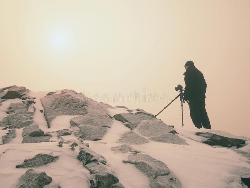 Travel photographer doing pictures in ancient stones on snowy peak of mountain. Winter morning royalty free stock image