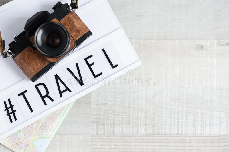 Travel and photography concept - top view of camera, map and lightbox with hashtag travel over wooden background royalty free stock photos