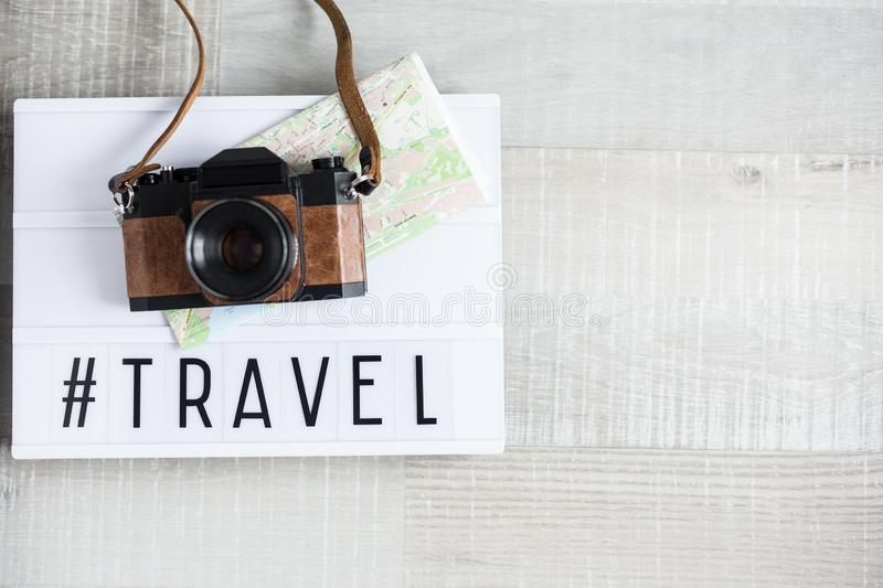 Travel and photography concept - top view of camera, map and lightbox with hashtag travel over wooden background with copy space royalty free stock photo