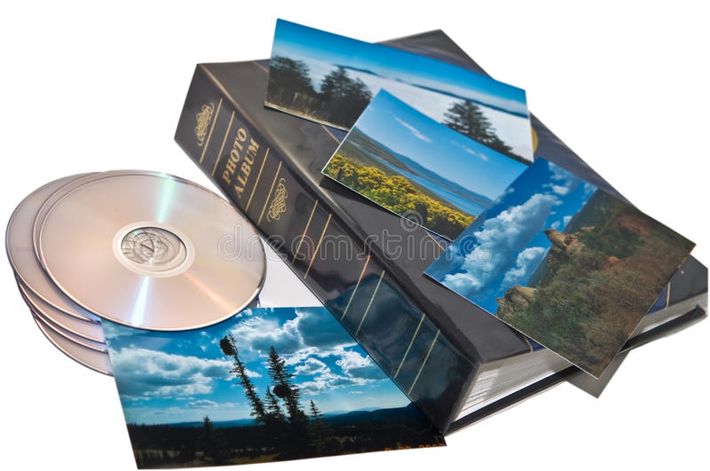Travel Photos CD and Album. A group of travel photos on top of a photo album with some CD's. Concept for backing up your images onto a CD or DVD for safety or stock photos