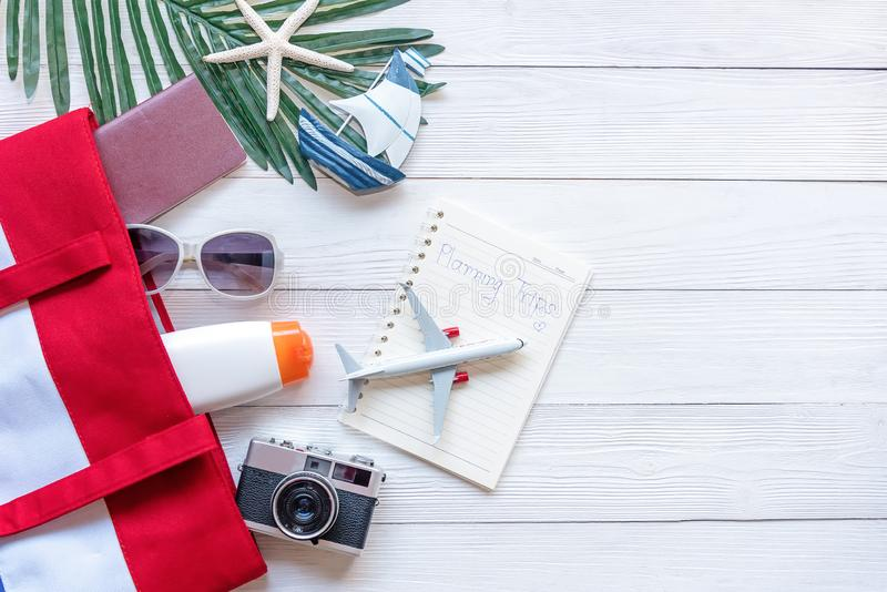 Travel Plan. Traveler planning trips summer vacations on the beach with Traveler accessories, retro camera, sunblock, sunglass, ai. Rplane and passport in royalty free stock photo
