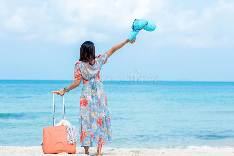 Travel Plan. women traveler holding orange luggage walking on the beach. Traveler and Tourism planning trips summer vacations royalty free stock images