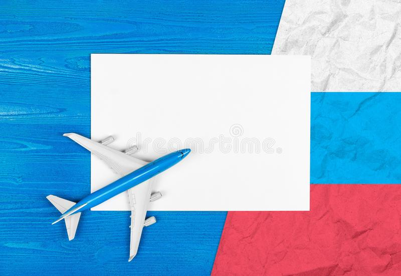 Model of airplane, blank sheet of paper and flag of Russia on the blue wooden background. Travel concept. royalty free stock images