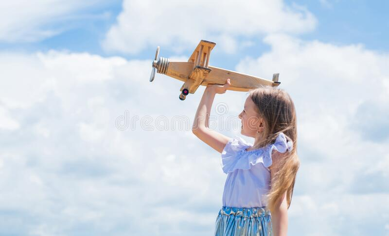 Travel by plane. Keep dreaming. kid play wooden toy airplane. Study geography. Dreams about travel. Story about summer. Vacation. small girl hold wooden plane royalty free stock images