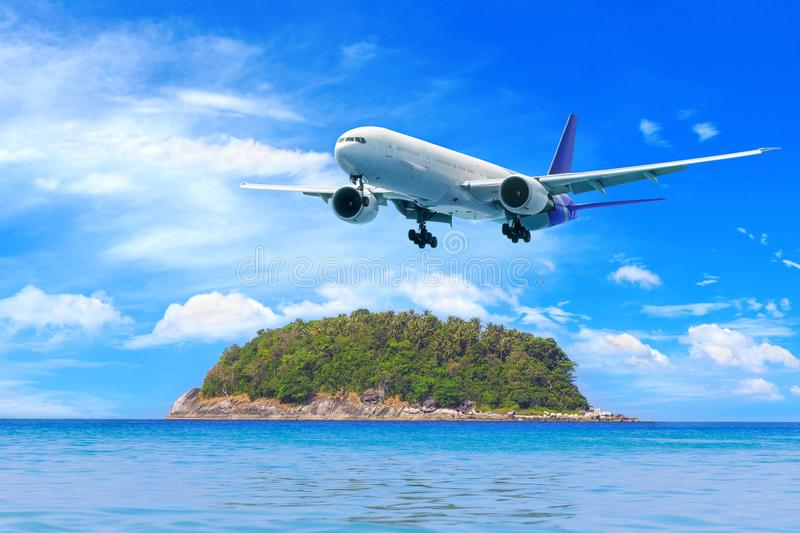 Passenger airplane flying above tropical island in Phuket, Thailand. Amazing view of blue sea and golden sand. royalty free stock images