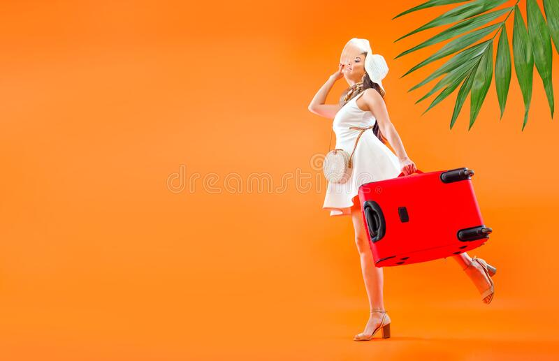 Travel preparation concept. Elegant woman in sundress and hat with wide brim holding a red travel suitcase in a hand. Upcoming trip. Summer vacation idea stock photography