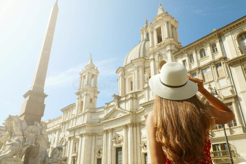 Travel in Rome. Back view of beautiful girl visiting Piazza Navona square landmark in Rome on sunny day. Summer holidays in Italy stock photo
