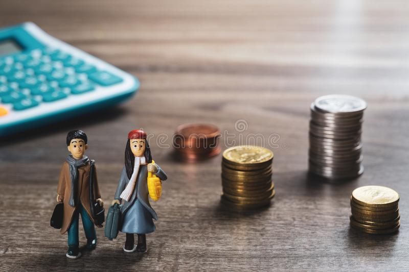 Travel saving and planing concept. couple people traveler miniature figure and stack of coins and calculator background. stock photo