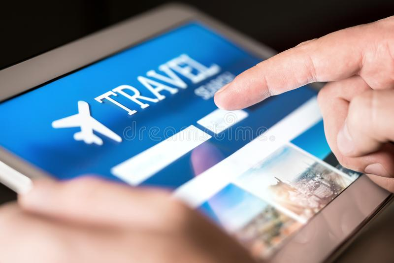 Travel search engine and website for holidays. Man using tablet to look for cheap flights and hotels. Online reservation for vacation tickets royalty free stock photography