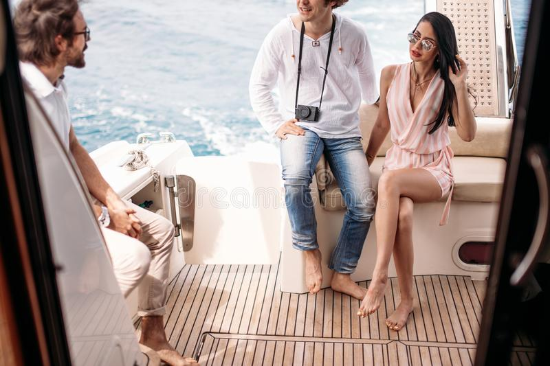 Travel, seatrip, friendship and people concept - friends sitting on yacht deck royalty free stock images