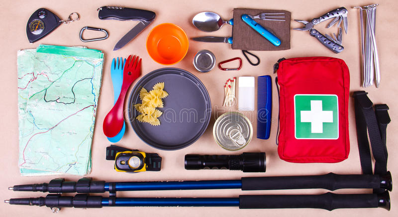 Travel set. Tourist outfit for camping or hiking. Various professional tools and items for outdoors pastime on beige background stock images
