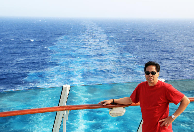 Travel by Ship. A handsome Filipino or Asian middle aged man posed by a ship railing, sailing in the middle of the ocean, traveling via ship or boat