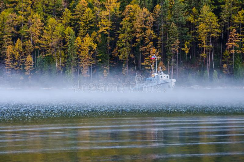 Travel ship with reflection and fog on lake Baikal at morning. With fog near forest stock images