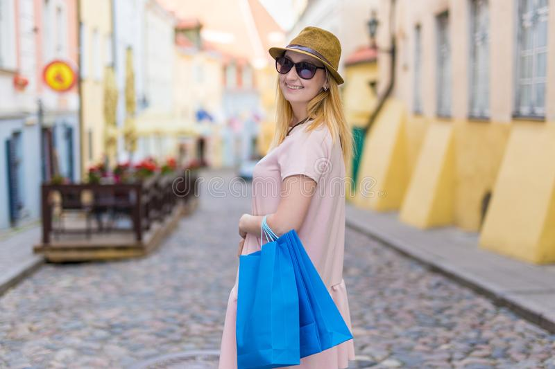 Travel and shopping concept - young happy woman walking in city stock image