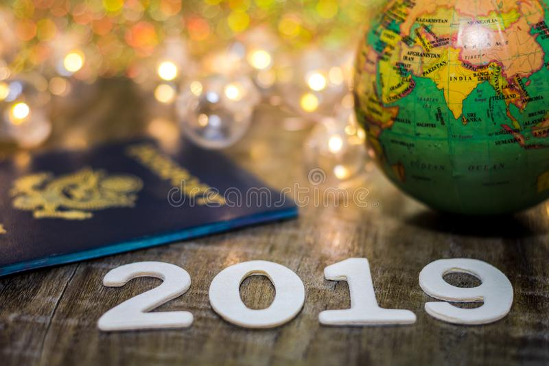 Travel 2019 still life concept with passport and fun lights on wooden board, shallow DOF. Travel still life concept with passport and fun lights on wooden board royalty free stock photo