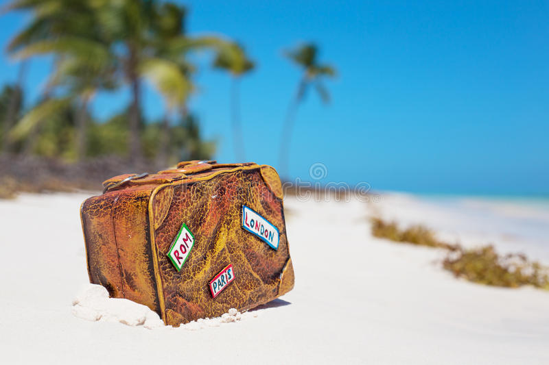 Travel suitcase toy on the beach royalty free stock photos