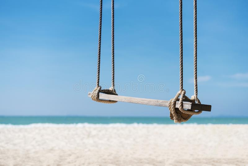 Travel and summer background, wooden swing on the beach with white sand, turquoise water and blue sky. Freedom life relax time. P stock image
