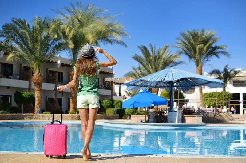 Travel, summer holidays and vacation concept - Beautiful woman walking near hotel pool area with pink suitcase stock photos