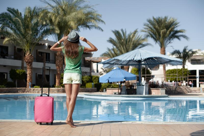 Travel, summer holidays and vacation concept - Beautiful woman walking near hotel pool area with pink suitcase stock photography