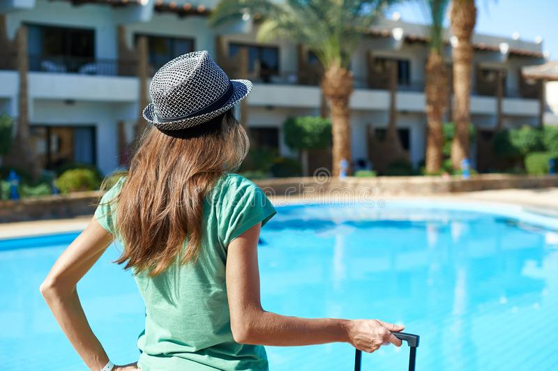 Travel, summer holidays and vacation concept - Beautiful woman walking near hotel pool area with suitcase in Egypt stock photo