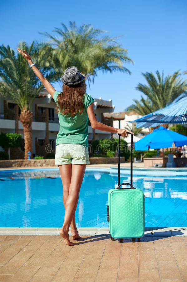 Travel, summer holidays and vacation concept - Beautiful woman walking near hotel pool area with turquoise suitcase in Egypt stock photo