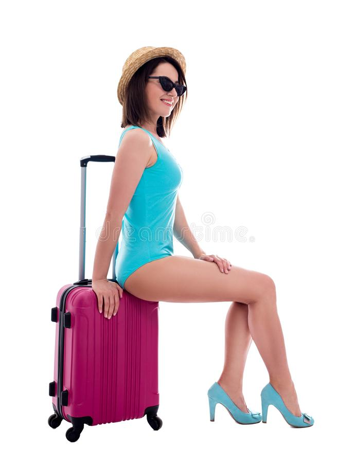 Travel and summer vacation concept - young beautiful woman in blue swimsuit sitting on suitcase isolated on white royalty free stock images