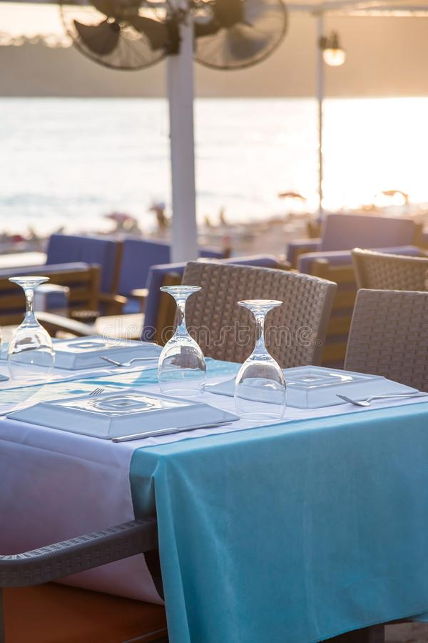 Travel table for lunch or dinner by the sea. A cafe table by the sea is covered with a tablecloth and served with appliances and glasses in the sunlight. Travel royalty free stock image