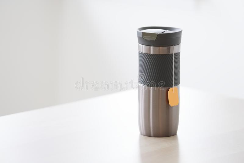 Travel thermal flask and hot tea drink with orange bag string hanging for travellers in outdoors with rubber grip. Uk stock images