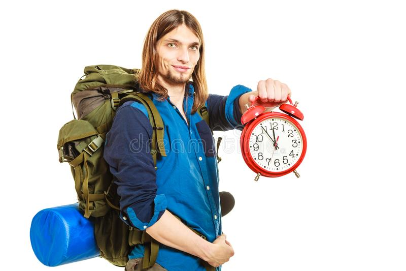 Travel time season. Man backpacker holding clock. Travel time season. Young man backpacker holding clock. Hiker on vacation summer trip journey. Last minute stock photography